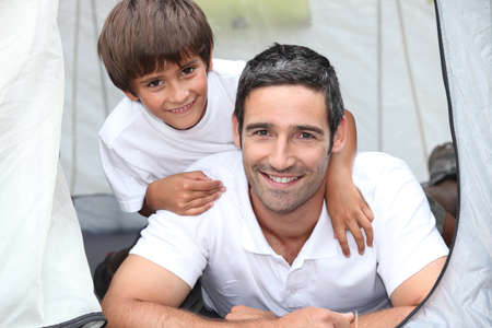 accomplices: father and son in tent Stock Photo