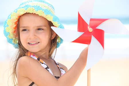 little girl at beach with toy windmill photo