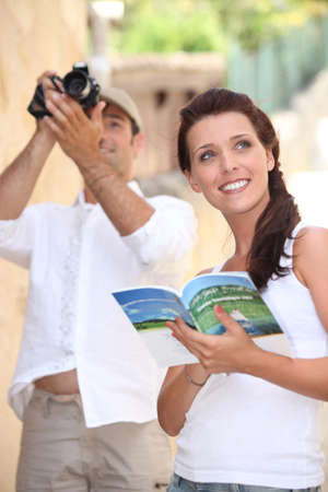 Tourists with camera and travel guide photo