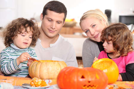 two parents and their two children celebrating Halloween photo