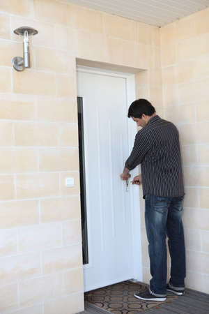 front entry: Man locking his door