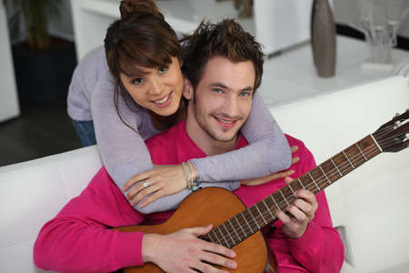 Woman beat guitar: Young couple playing a guitar at home Kho ảnh