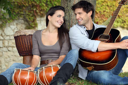 long weekend: Couple playing drums and a guitar under a tree Stock Photo