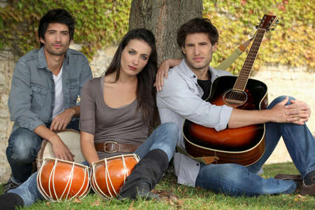 Woman beat guitar: three musicians at the foot of a tree