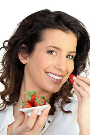 Woman eating strawberries photo