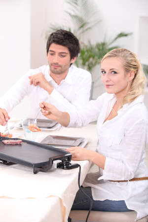 couple dining: Couple cooking meat on a tabletop electric plate