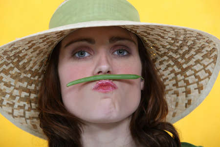 Woman balancing a green bean between her lips and her nose Stock Photo - 11775068