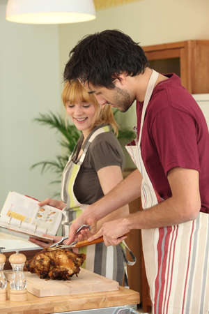 Couple preparing a meal together with the help of a cookbook photo