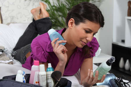 Woman looking at lotion bottles photo