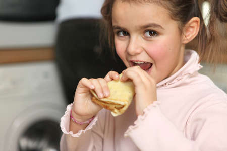 Little girl eating pancake photo