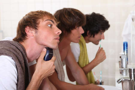 Three young men in the bathroom getting ready to go out photo