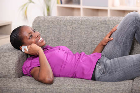 woman lying on settee with mobile phone photo