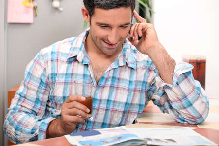 Man with a magazine and cellphone Stock Photo - 11776358