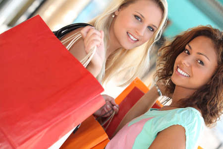 on line shopping: girls in shopping frenzy Stock Photo