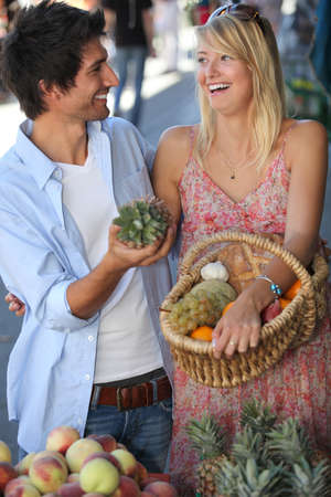 Young couple laughing in a market photo