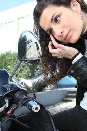 Woman applying eye make-up with the help of her motorcycle photo