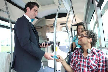 chofer de autobus: Un controlador de joven el control de pasajeros en un autob�s. Foto de archivo