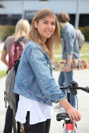 16 17: Smiling teenage girl with bicycle Stock Photo