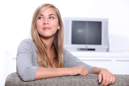 Smiling young woman sitting on a couch with a television set in the background Stock Photo - 11775018