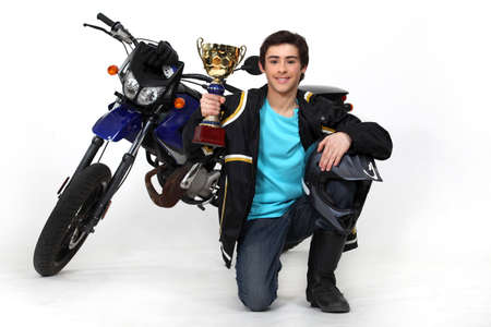 Teenager with gold cup in front of a motorbike photo