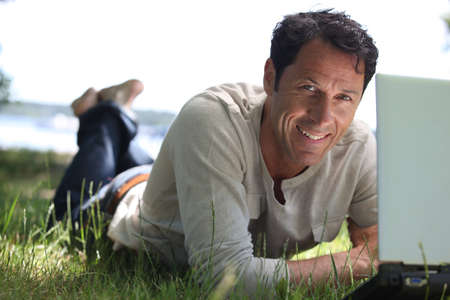 40 45: Man smiling working on the grass Stock Photo