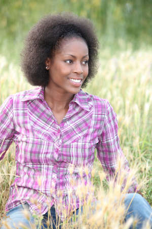 black woman sitting and relaxing in a field photo