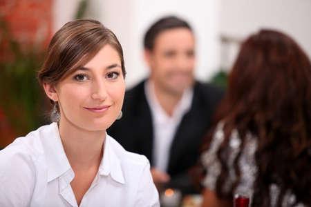 unmarried: Centrarse en una mujer sentada en un restaurante con otros comensales en el fondo