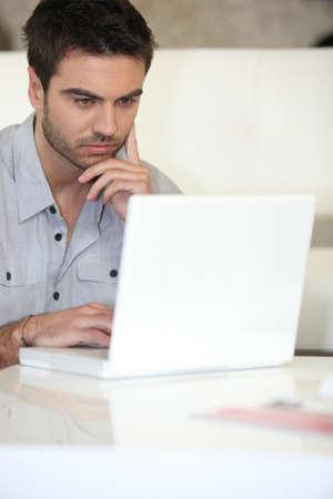 Pensive man using laptop at home photo