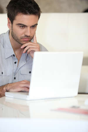relaxed man: Pensive man using laptop at home Stock Photo