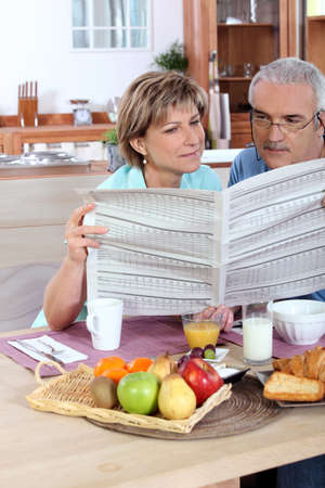 Middle-aged couple reading photo