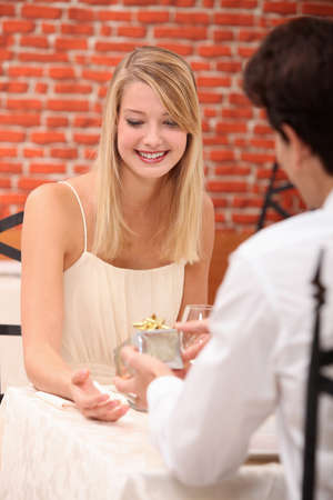 Young woman receiving a present in a restaurant photo