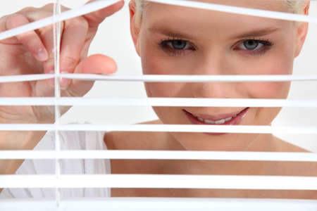 Woman peering through blinds Stock Photo - 11774796