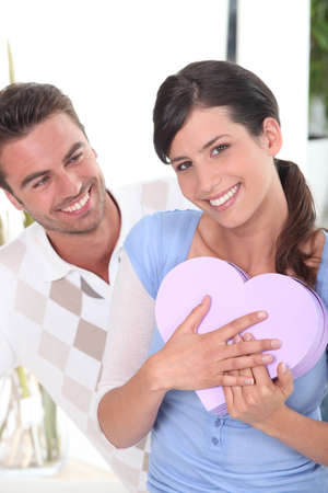 Man giving his girlfriend chocolates photo