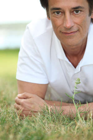 facing to camera: Man smiling laid on the grass