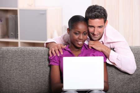 Couple sat at home looking at laptop computer photo