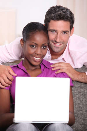 Interracial couple with a laptop. photo