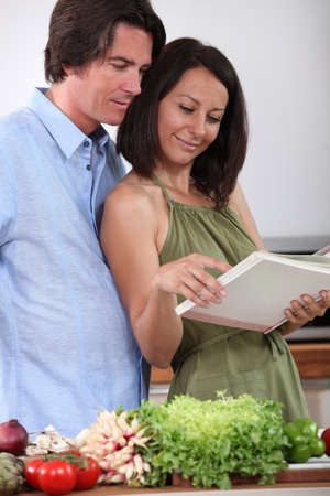 Couple watching cookbook in a kitchen photo