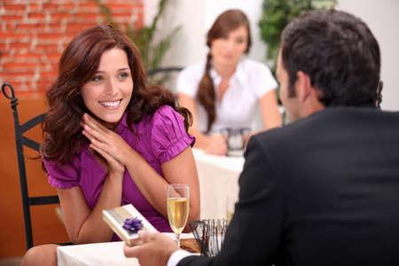 amigas conversando: mujer feliz de recibir un regalo en el restaurante