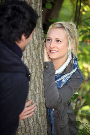 attachments: a blonde woman watching lovingly a man in the forest