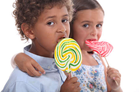 childhood obesity: couple of children with lollypops