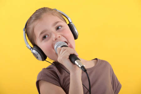 Little girl with microphone and headphones photo