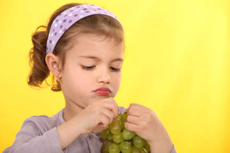 A little girl eating grapes. photo