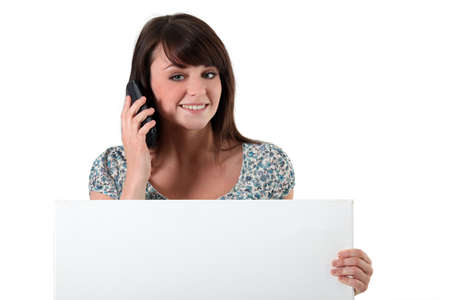 Young woman with a cellphone and a board left blank for your message Stock Photo - 11774285