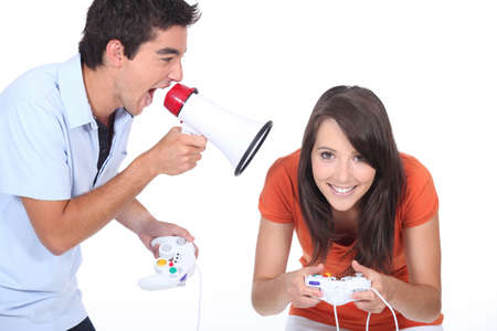 narration: Man shouting into megaphone as girlfriend plays video game