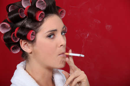 Woman smoking with her hair in rollers Stock Photo - 11775299