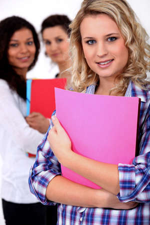 bookish: Young woman at school with her friends Stock Photo