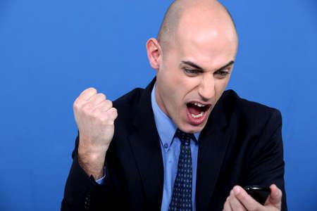 Angry bald businessman holding telephone Stock Photo - 11774800