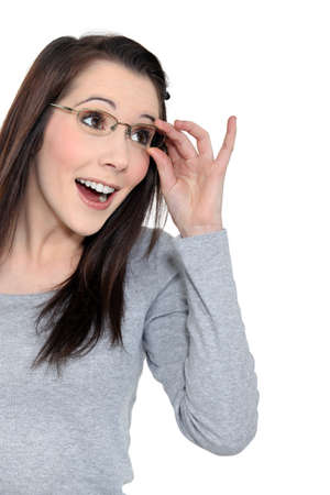 eyes contact: Surprised woman holding her glasses