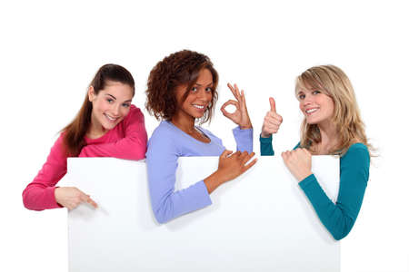 non verbal communication: Women enthusiastically holding up a blank sign