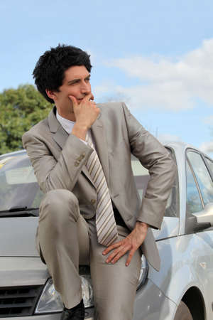 apprehension: Businessman thinking by his car